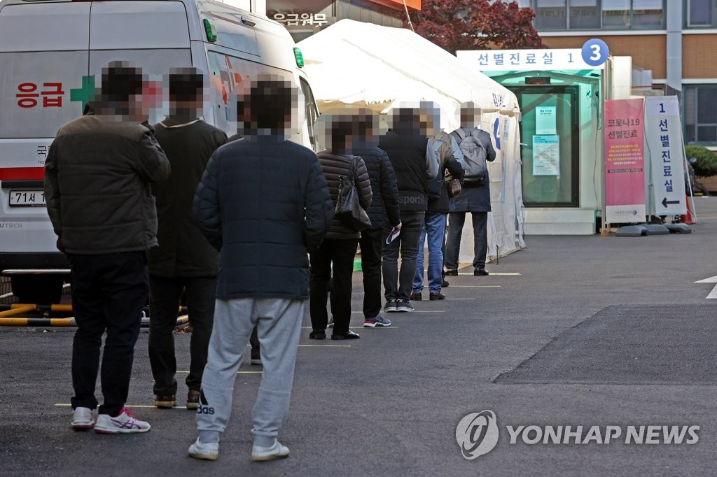 資料圖片:11月9日,在新冠篩查站外,人們排隊候檢。 韓聯社