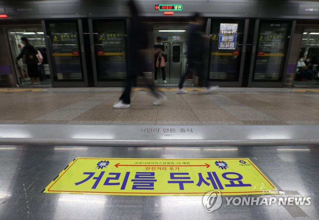 資料圖片:11月19日,首爾市光化門地鐵站內部貼著宣傳保持社交距離的告示。 韓聯社