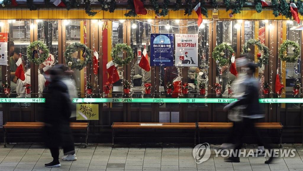 資料圖片:年底降至,疫情再度擴散。圖為首爾一家餐廳門口,攝于11月19日。 韓聯社