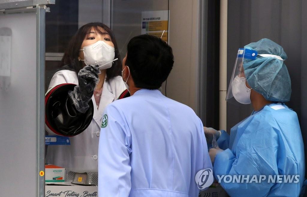 資料圖片:醫務人員正在接受新冠病毒檢測。 韓聯社