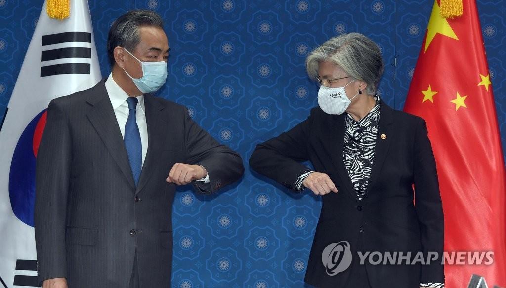 11月26日,在首爾外交部大樓,南韓外交部長官康京和(右)和到訪的中國外交部長王毅在會談開始前用肘擊替代握手致意,併合影留念。 韓聯社/聯合攝影團