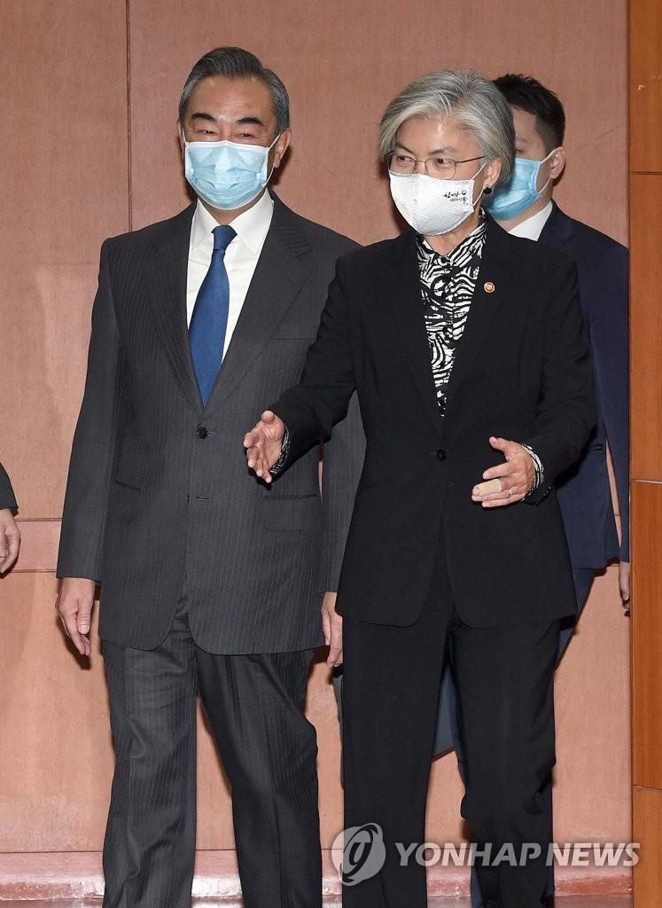 11月26日,在首爾外交部大樓,南韓外交部長官康京和(右)和到訪的中國外交部長王毅走向會場。 韓聯社/聯合攝影團