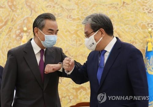 王毅和韓幕僚長碰肘致意