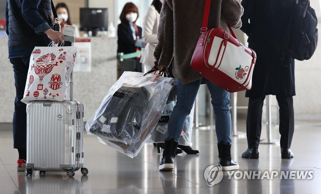 資料圖片:2020年12月12日,在仁川國際機場,國際低空遊的乘客正拿著購買的免稅品進入登機口。 韓聯社