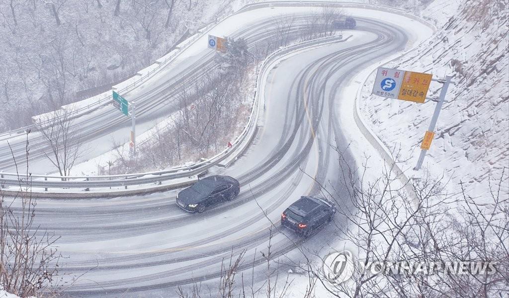 資料圖片:12月13日,在江原道寒溪嶺,車輛行駛在下過雪的路上。 韓聯社/讀者供圖(圖片嚴禁轉載複製)