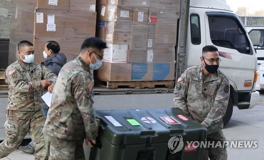 資料圖片:2020年12月28日,在位於京畿道平澤市的駐韓美軍基地,美國國防部為駐韓美軍提供的新冠疫苗運抵南韓。圖為相關人員搬運疫苗。 韓聯社/駐韓美軍供圖(圖片嚴禁轉載複製)