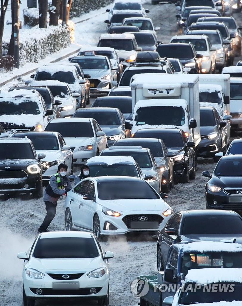 資料圖片:1月7日上午,在京畿道水原市靈通區光教路一帶,連夜強降雪導致早高峰交通嚴重受阻。圖為交警在雪路上推出被困車輛。 韓聯社