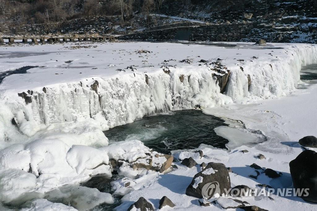 1月7日,在江原道鐵原郡漢灘江直湯瀑布,瀑布被凍成一面冰�晼C 韓聯社