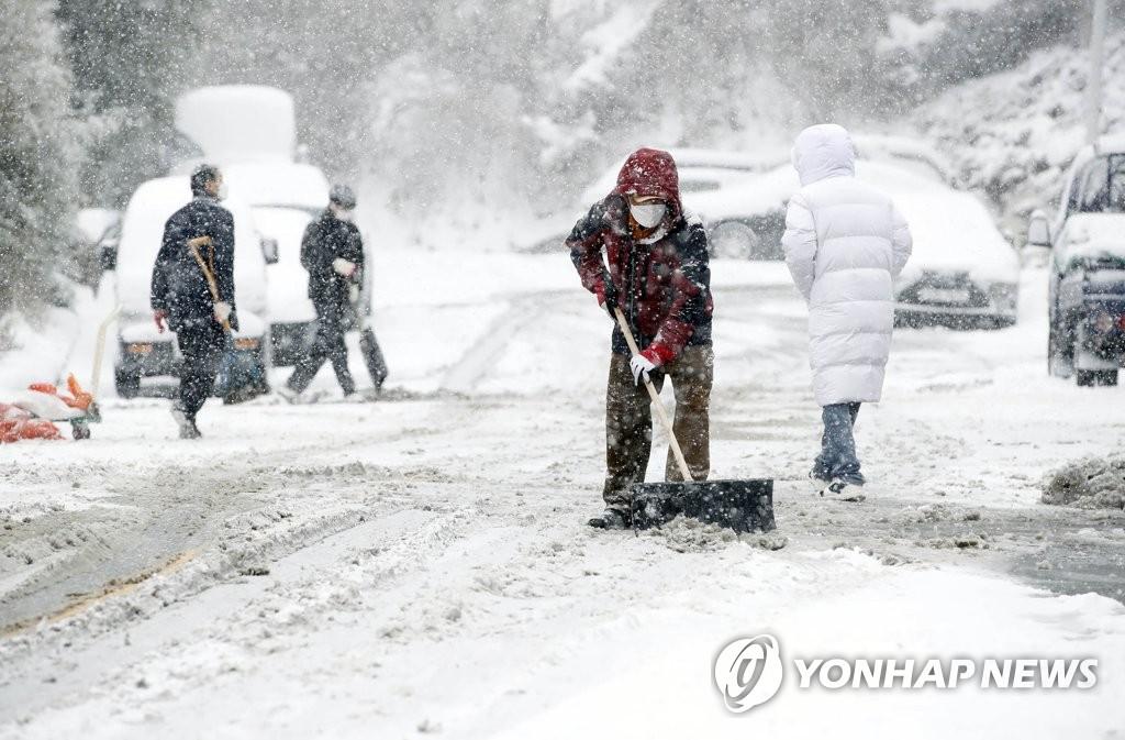 1月7日,在光州北區雲岩3洞的一條道路上,工作人員清掃路上的積雪。 韓聯社/光州北區政府供圖(圖片嚴禁轉載複製)