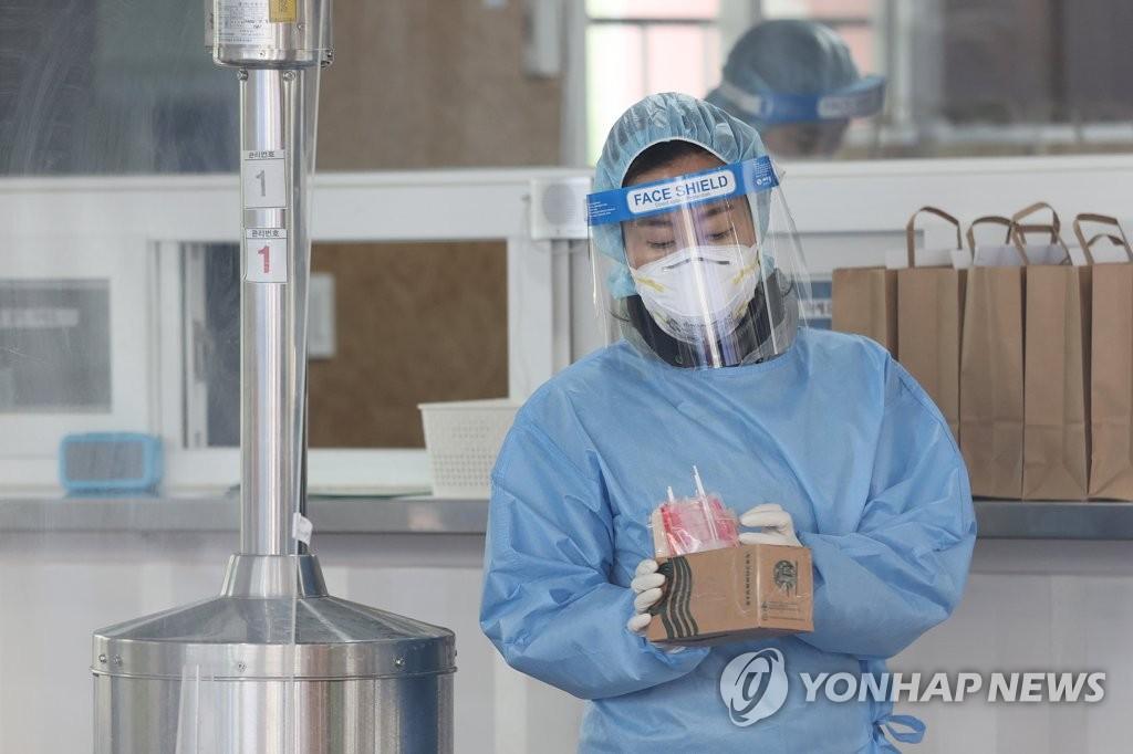 2月22日下午,在首爾市銅雀區衛生所,一名護士手持試劑盒準備進行核酸檢測採樣。 韓聯社