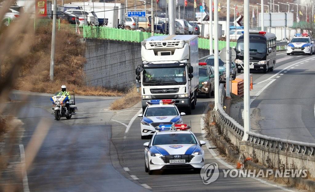 2月24日,一輛裝載阿斯利康新冠疫苗的運送車輛在警車的護送下前往位於京畿道利川市的物流中心。 韓聯社