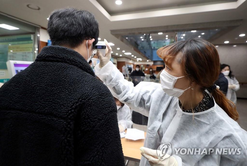 2月26日上午,在仁川市富平區衛生所,工作人員正在為預防接種者測體溫。 韓聯社