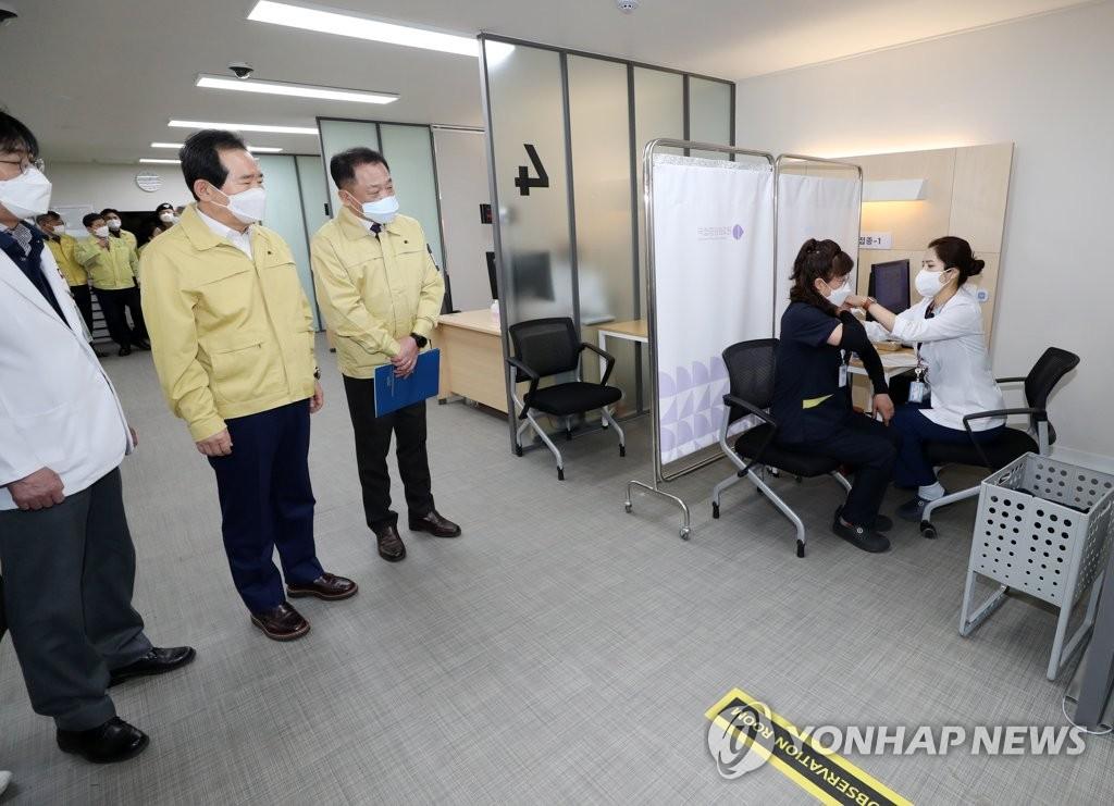 2月27日,南韓務總理丁世均(左二)視察接種現場。 韓聯社