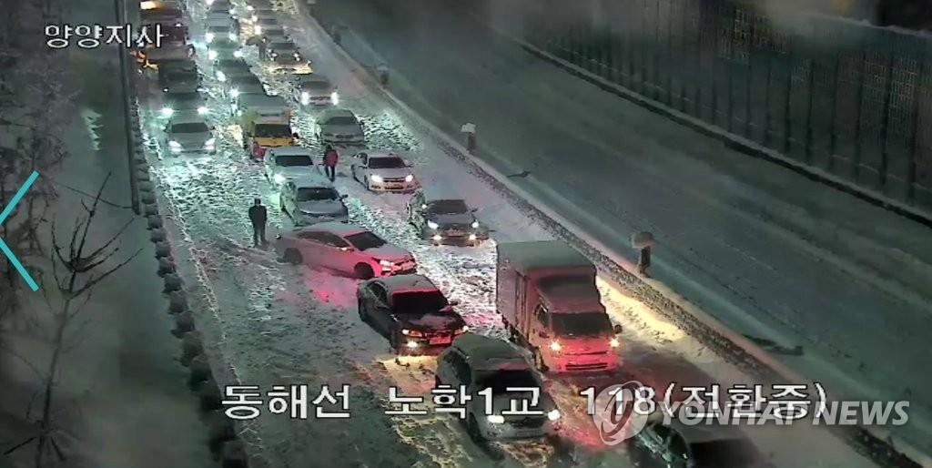 資料圖片:3月1日,東海高速公路附近的車輛被困雪中。 南韓道路公社監控視頻截圖(圖片嚴禁轉載複製)