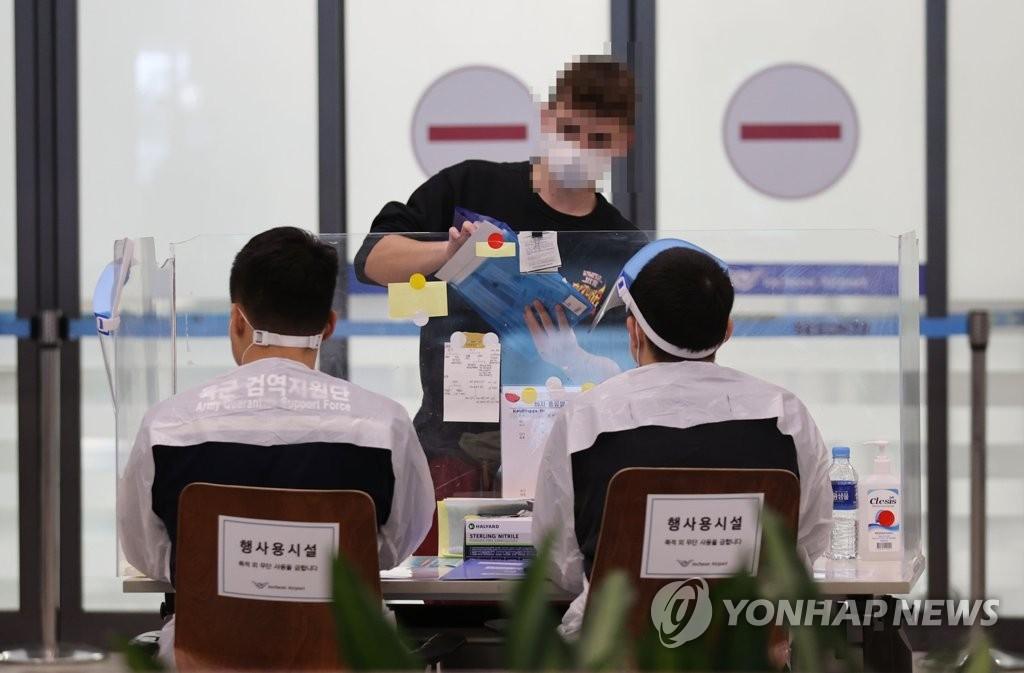 資料圖片:3月15日,在仁川國際機場第一航廈,防疫工作人員為海外入境者提供指引。 韓聯社