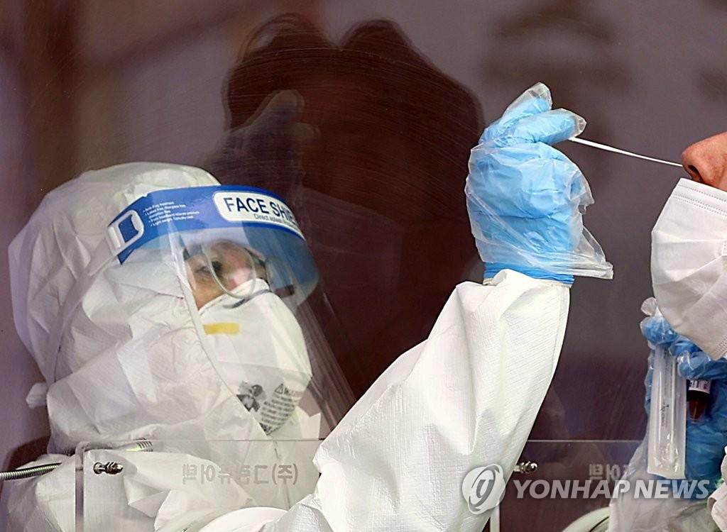 資料圖片:醫務人員採樣。 韓聯社