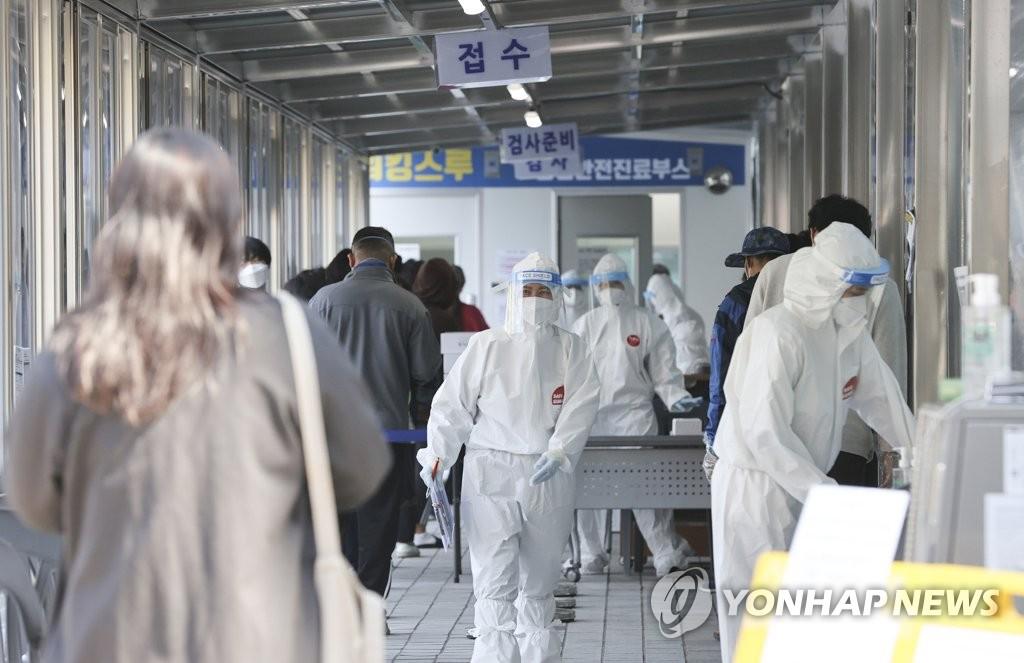 資料圖片:4月7日,在首爾東大門區衛生站的臨時篩查診所,市民等待接受病毒檢測。 韓聯社