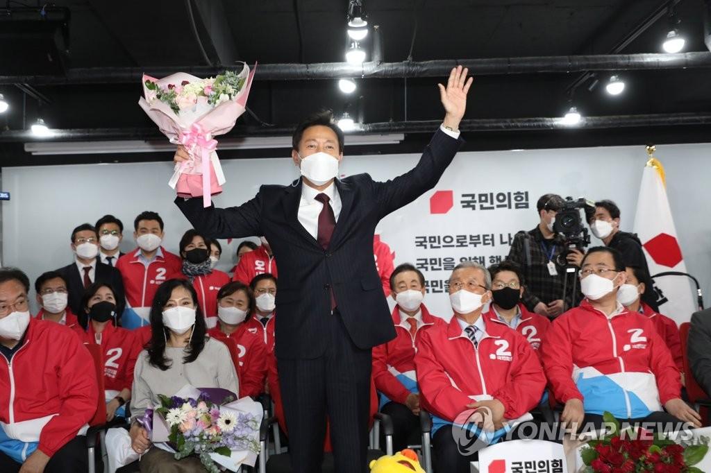 4月8日,在位於首爾汝矣島的最大在野黨國民力量辦公樓,首爾市長補選國民力量候選人吳世勳手舉起花束慶祝。 韓聯社