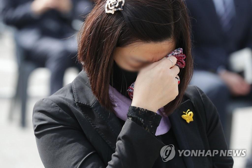 """4月16日,在京畿道安山市花郎遊樂園,出席""""世越""""號沉船事故遇難者悼念儀式的市民忍不住流淚。 韓聯社"""