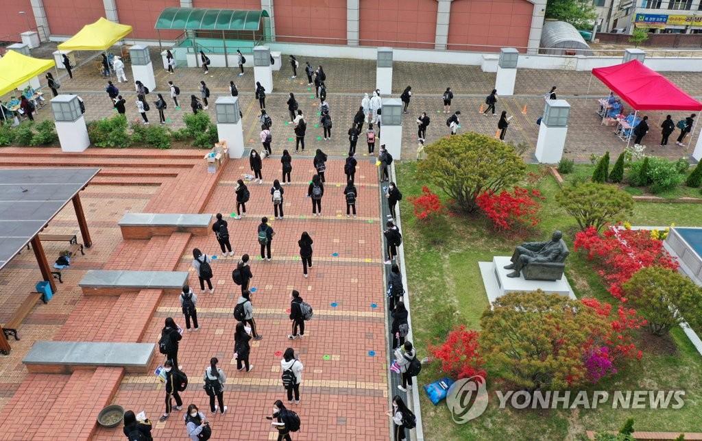 資料圖片:4月22日下午,在光州市北區一所高中,學生們排隊等候核酸篩查。 韓聯社