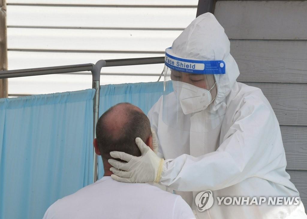 資料圖片:5月3日,在設于江原道江陵市原長途巴士候車室的臨時篩查診所,一名外籍勞工接受新冠檢測。 韓聯社