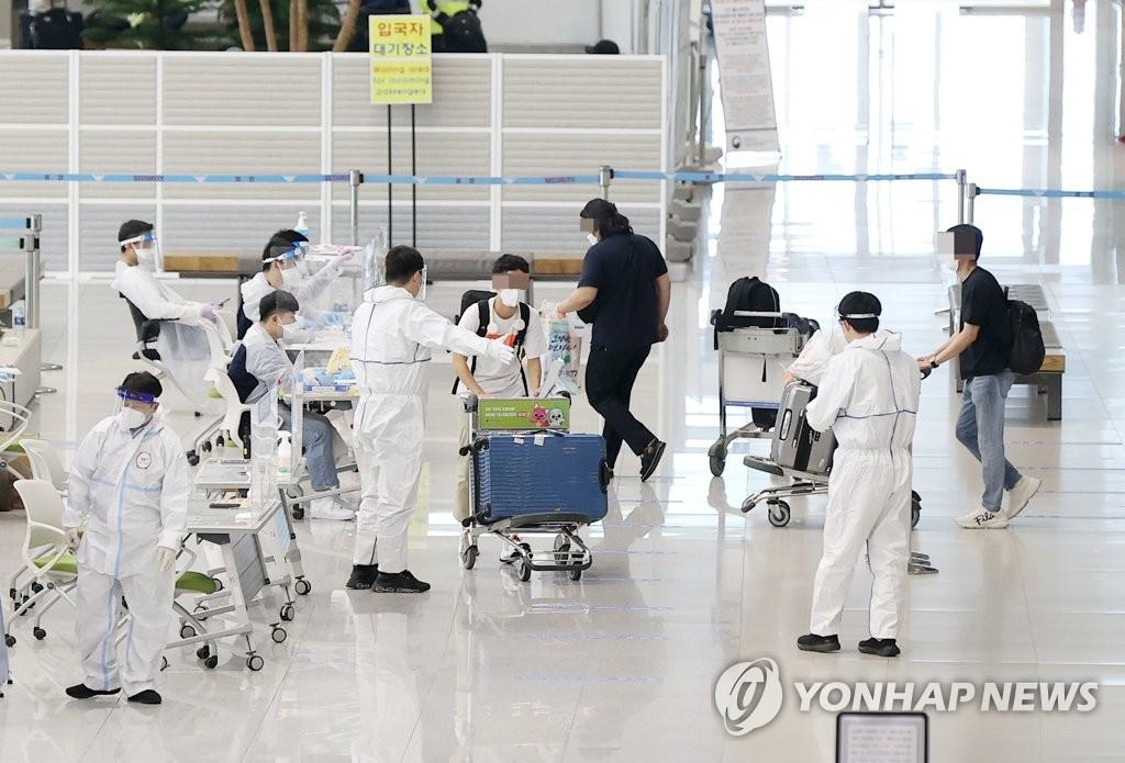 資料圖片:5月5日,在仁川國際機場第二航廈到達大廳,工作人員引導入境者入境。 韓聯社