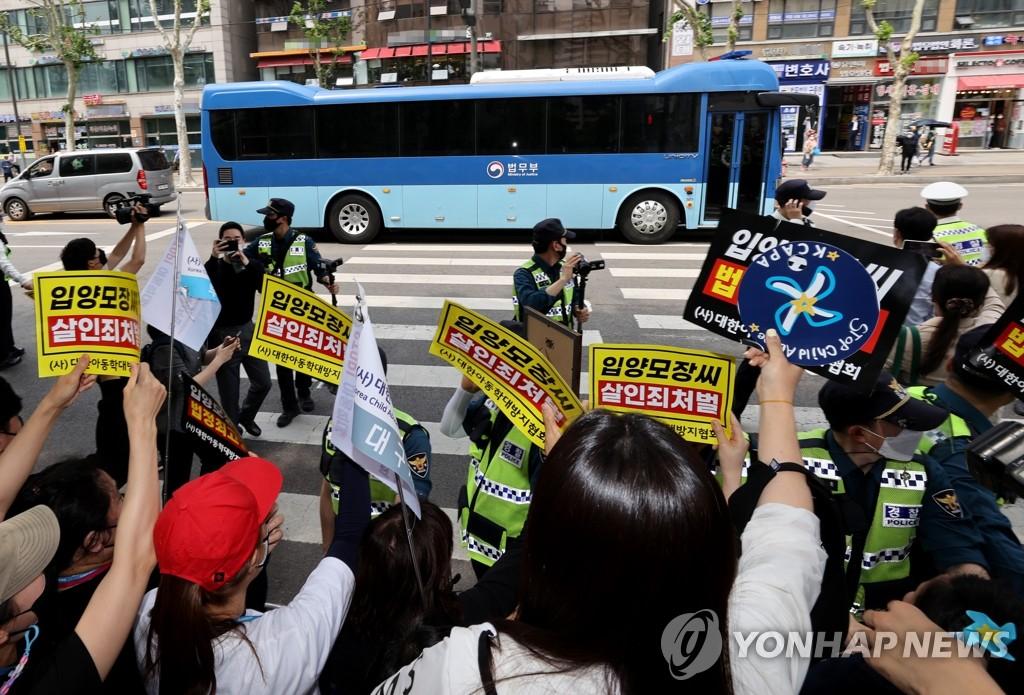 """5月14日,在審理""""鄭仁""""案的首爾南部地方法院前,市民向主犯張某乘坐的車輛舉牌抗議。 韓聯社"""
