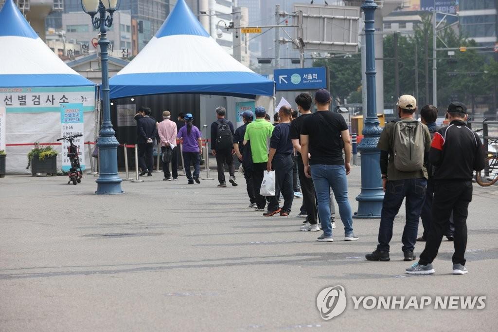資料圖片:6月6日,在首爾火車站的臨時篩查診所,市民們排隊候檢。 韓聯社