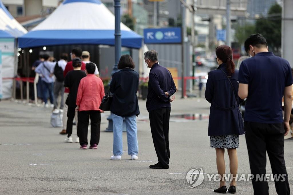 資料圖片:6月9日,在首爾站廣場的臨時篩查診所前,人們排隊待檢。 韓聯社