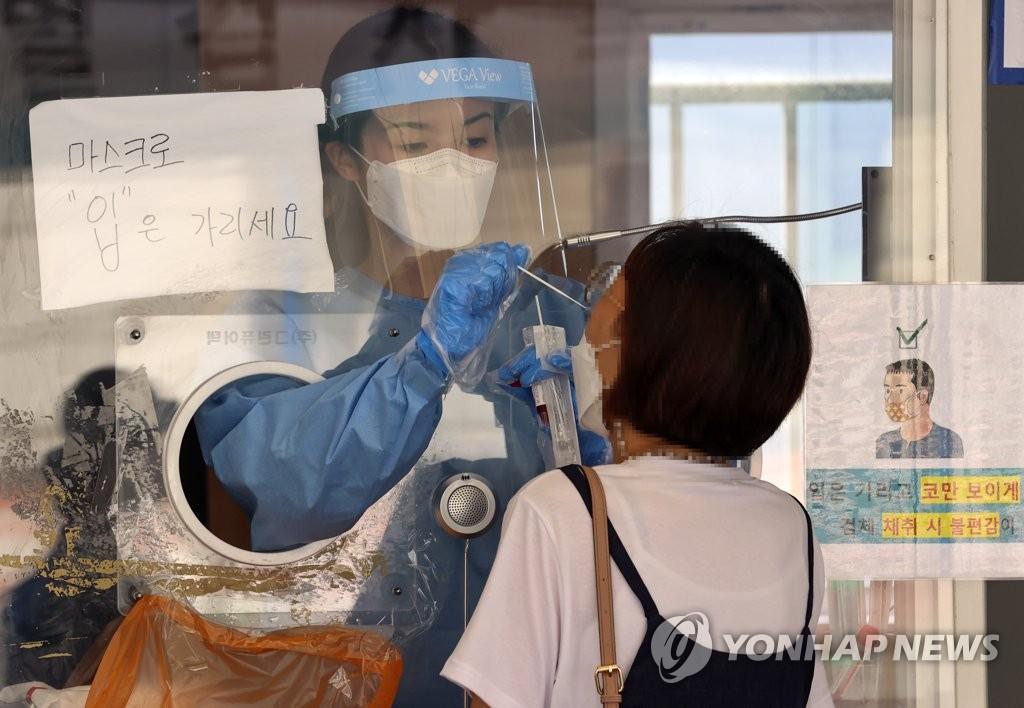 資料圖片:6月9日上午,在首爾站廣場的臨時篩查診所,一位市民正在接受新冠檢測。 韓聯社