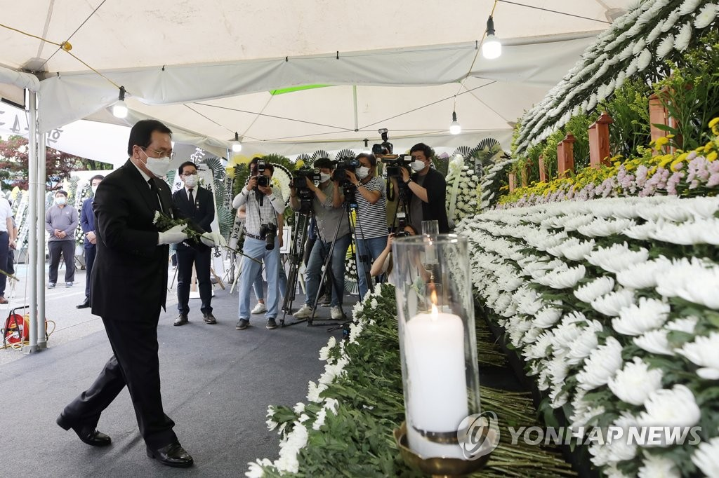 6月11日下午,在光州市東區區政廳停車場,俞英民向拆樓倒塌事故遇難者靈前獻花。 韓聯社