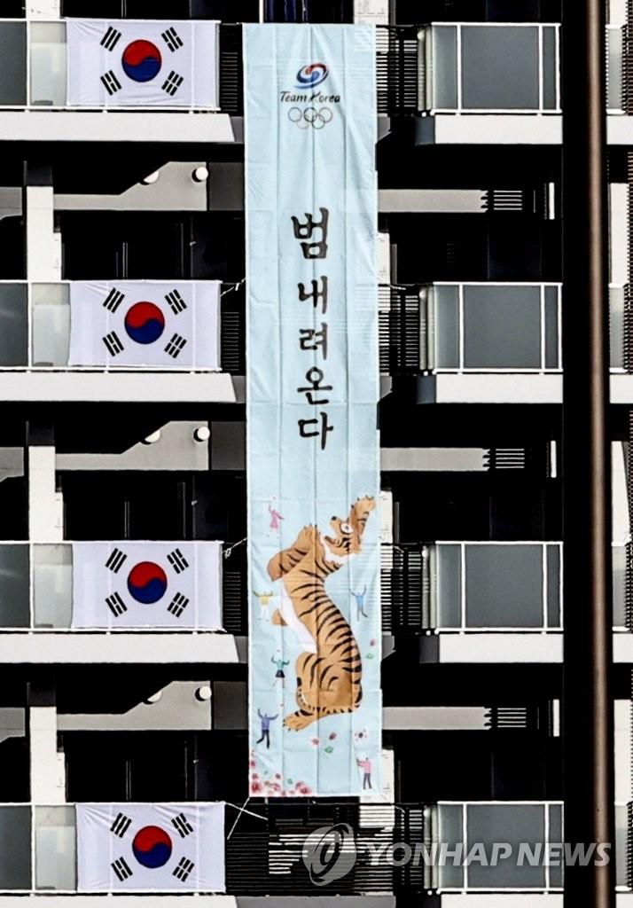 """7月18日,在位於東京晴海的東京奧運村,南韓代表團在宿舍樓外懸挂""""猛虎下山""""條幅。 韓聯社"""