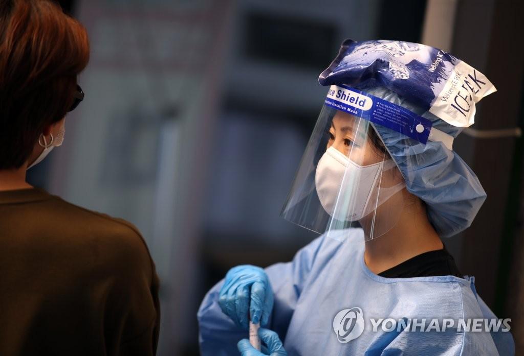 資料圖片:7月21日,在首爾銅雀區衛生站的篩查診所,一名醫務人員身穿防護服,頭頂冰袋消暑。 韓聯社