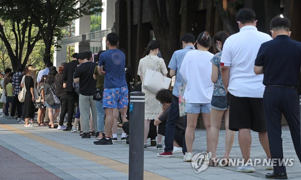 資料圖片:7月22日,在首爾松坡區衛生站的篩查診所,市民排隊待檢。 韓聯社