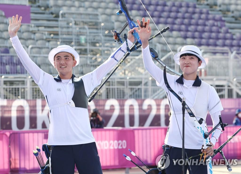 7月24日,在東京夢之島公園,南韓射箭運動員金濟德(左)和安山舉起金牌慶祝奪金。在當天下午進行的東京奧運會射箭混合團體決賽上,金濟德/安山組合以5比3力壓荷蘭隊,奪得金牌。 韓聯社