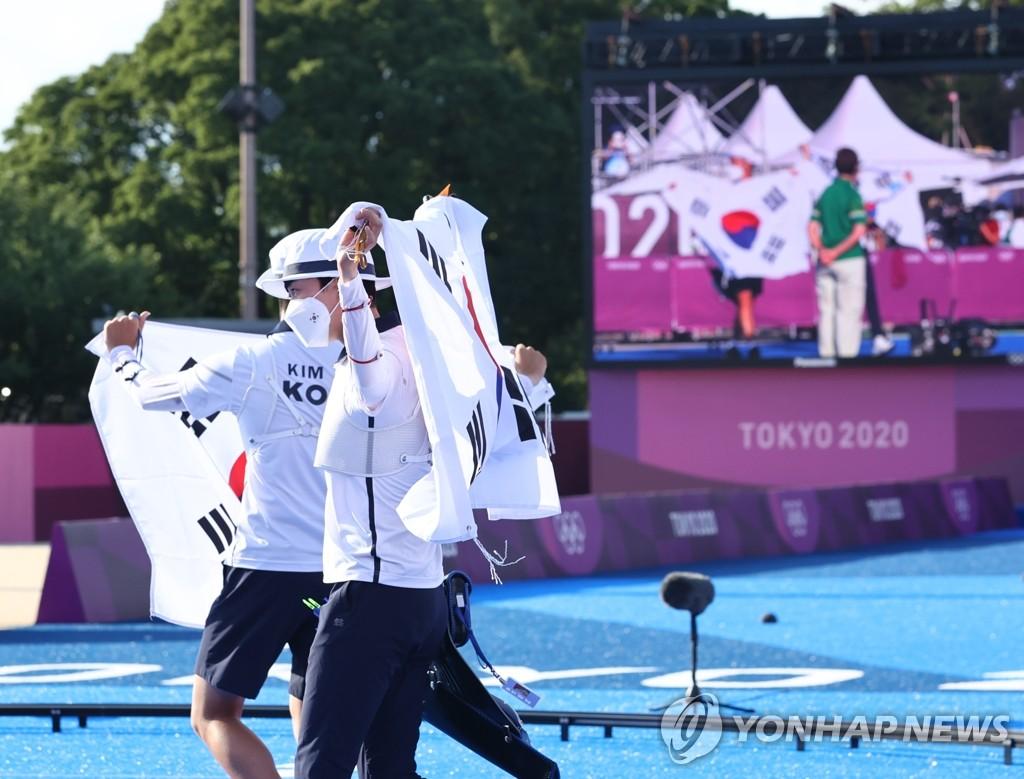 7月24日,在東京夢之島公園,南韓射箭運動員金濟德和安山奪金後舉旗慶祝。在當天下午進行的東京奧運會射箭混合團體決賽上,金濟德/安山組合以5比3力壓荷蘭隊,奪得金牌。 韓聯社