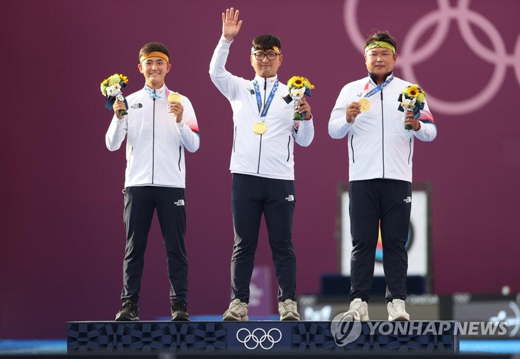 7月26日,在日本東京夢之島公園射箭場,南韓男子射箭隊隊員金濟德(左起)、金優鎮、吳真爀在頒獎典禮上手舉金牌開心合影。南韓隊在東京奧運射箭項目男子團體決賽上以6-0大勝中華台北隊,實現了奧運兩連冠。 韓聯社