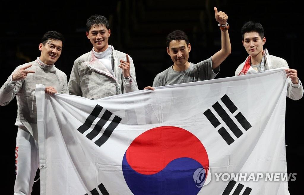 7月28日,東京奧運男子團體佩劍決賽在日本千葉幕張展覽館舉行。由吳尚旭、具本佶、金政煥和替補的金準鎬組成的南韓擊劍隊以45比26的比分戰勝義大利奪冠。圖為南韓隊舉國旗合影。 韓聯社
