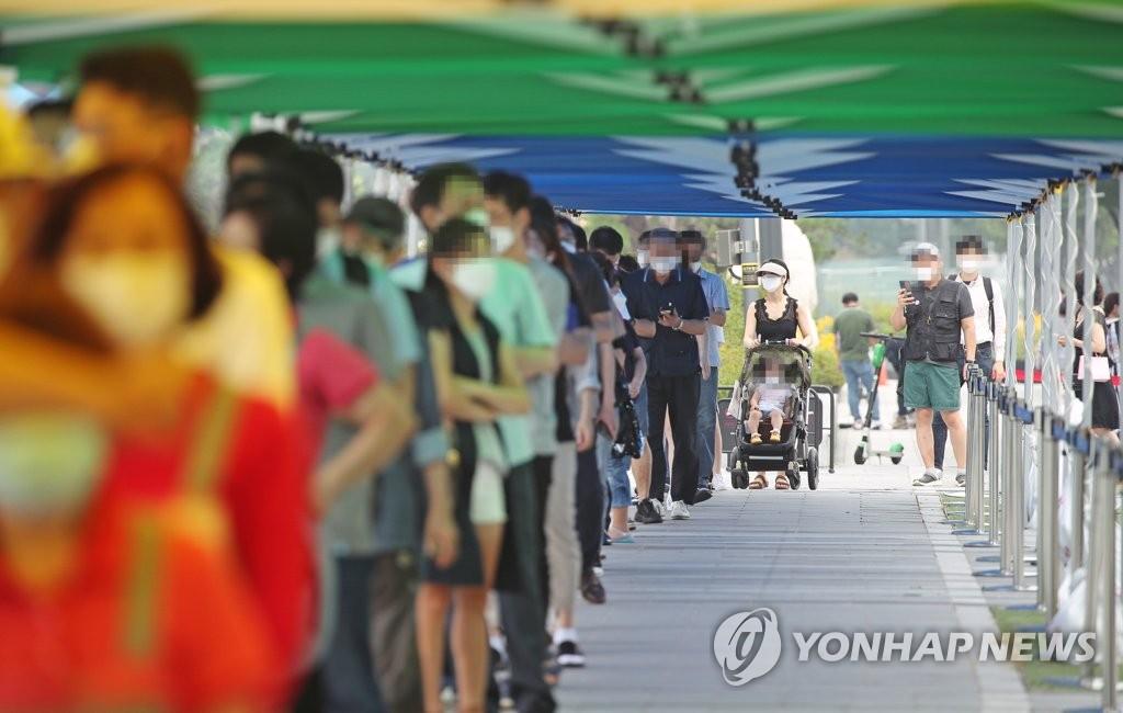 資料圖片:7月29日,在首爾江南地區COEX前設置的臨時篩查診所,人們排隊等待核酸檢測。 韓聯社