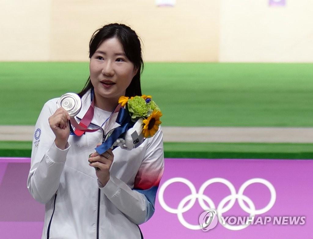 7月30日,在日本東京朝霞射擊訓練場,南韓射擊運動員金珉靜在東京奧運女子25米手槍決賽上斬獲銀牌。圖為金珉靜在頒獎儀式上展示銀牌。 韓聯社
