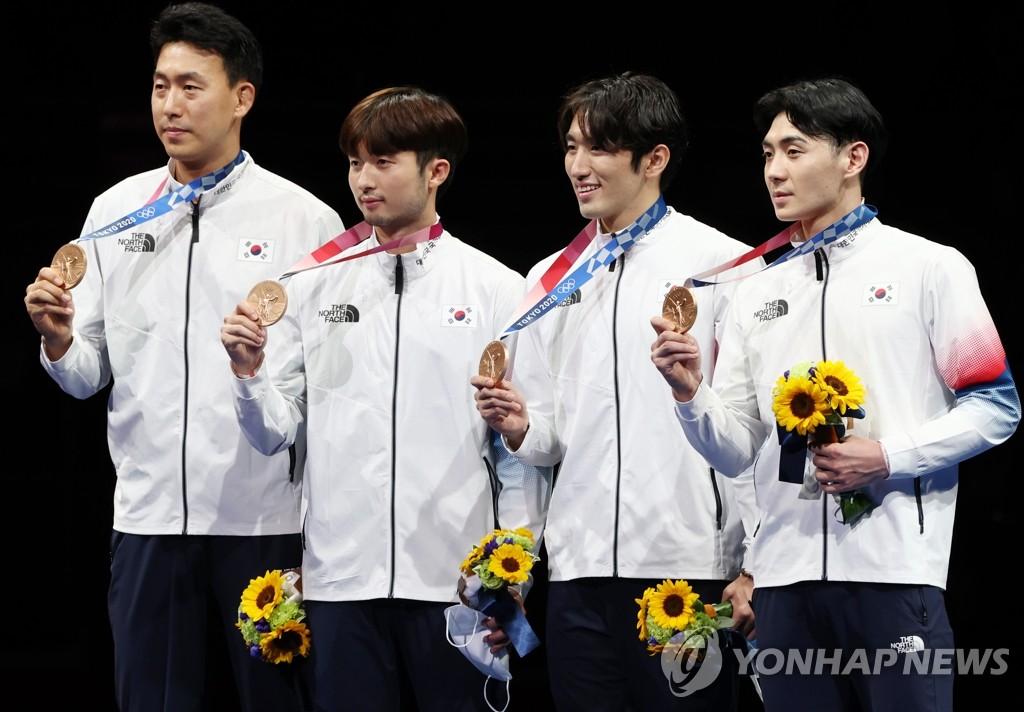 7月30日,在日本幕張展覽館舉行的東京奧運會男子團體重劍銅牌賽中,南韓隊以45比41戰勝中國隊,實現男子重劍獎牌零的突破。圖為南韓男子重劍隊在頒獎儀式上舉銅牌合影。 韓聯社