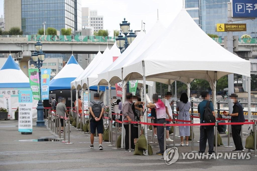 7月31日,在設于首爾站廣場的臨時篩查診所,市民排隊待檢。 韓聯社