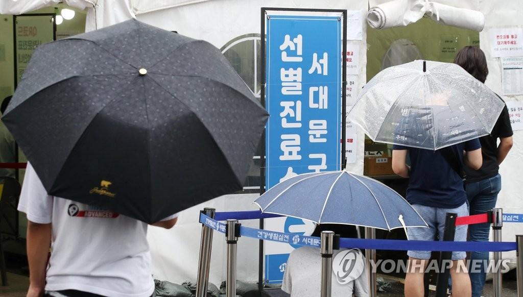 資料圖片:8月1日,在首爾西大門區江衛生站前設置的臨時篩查診所,人們撐傘排隊等待核酸檢測。 韓聯社