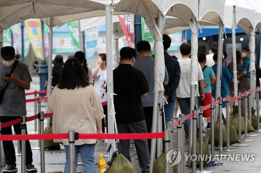 資料圖片:在一處新冠臨時篩查診所,市民排隊候檢。 韓聯社