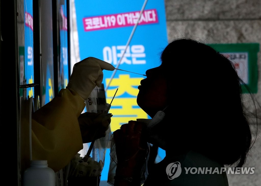 資料圖片:8月3日,在首爾恩平區舊擺撥站臨時篩查診所,一位市民正在接受新冠病毒核酸檢測採樣。 韓聯社