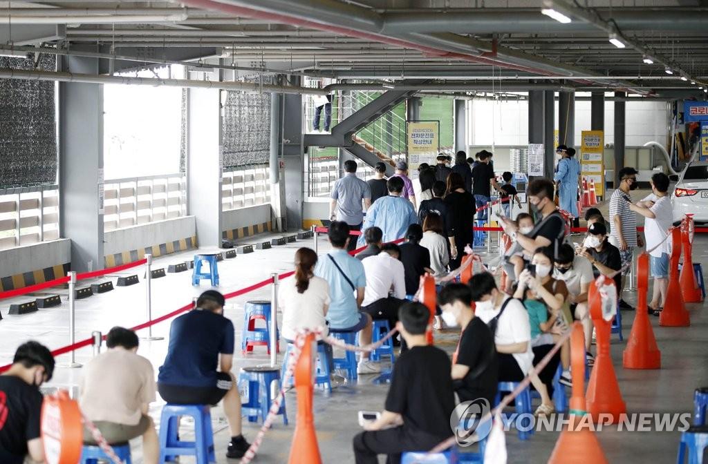 資料圖片:8月3日,在光州北區篩查診療所,市民們排長隊等待檢測。 韓聯社