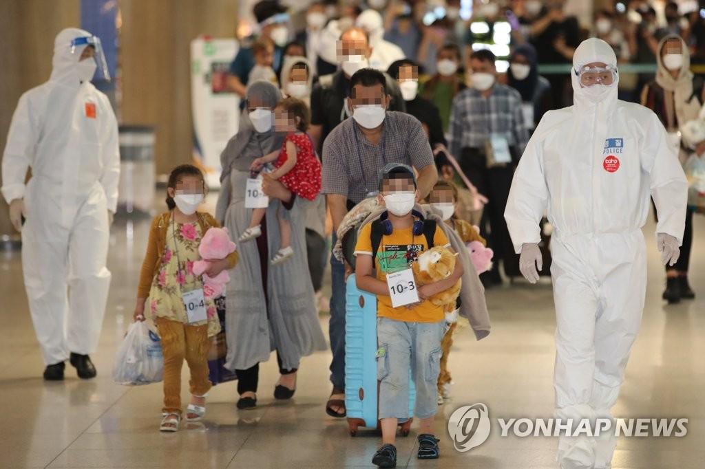 資料圖片:8月26日,在仁川國際機場,第一批曾協助南韓政府活動的阿富汗人及其家屬乘坐南韓空軍多功能空中加油運輸機抵達南韓。圖為他們在接受核酸檢測後,按照工作人員的指示走出機場。 韓聯社