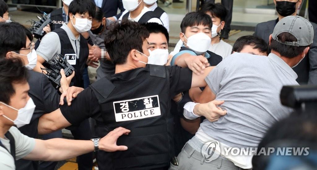 """9月7日,在首爾松坡警察署,涉嫌在破壞追蹤位置""""電子腳鐐""""前後殺害兩名女性的犯罪嫌疑人姜允誠被送檢。圖為警察阻止一名市民(右一)靠近。 韓聯社"""