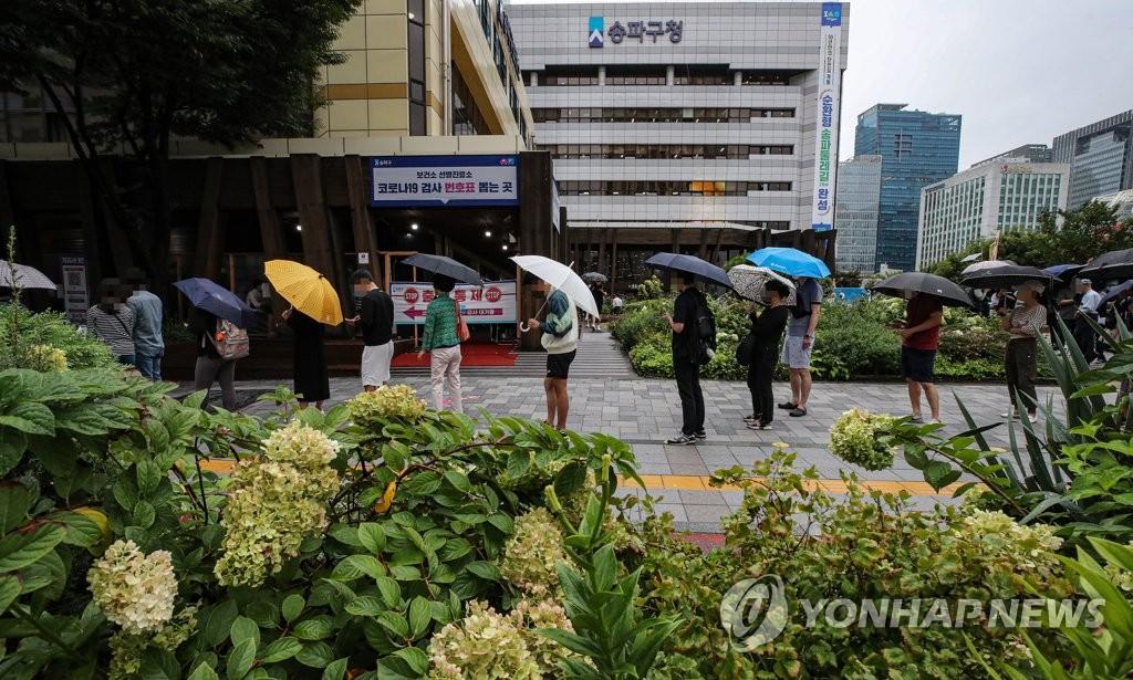 9月7日,在設于首爾松坡區衛生站的篩查診所,市民們撐傘排隊等待接受病毒檢測。 韓聯社