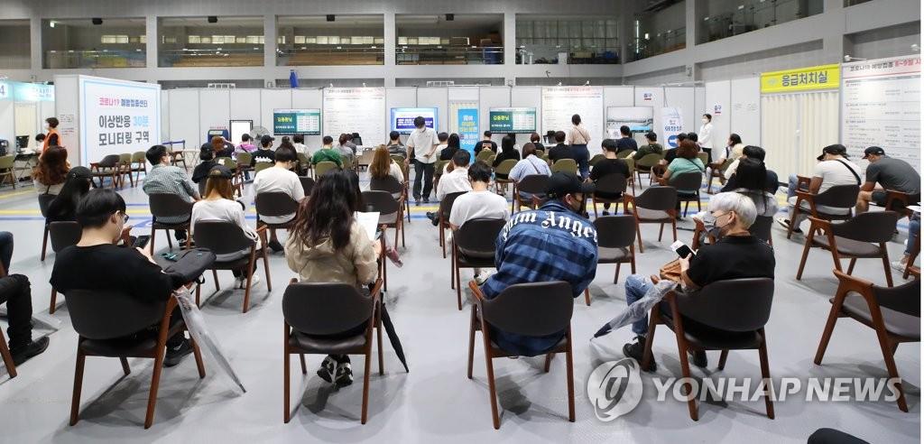 資料圖片:9月7日,在設于首爾麻浦區民體育中心的接種點,市民施打新冠疫苗後觀察是否出現異常反應。 韓聯社
